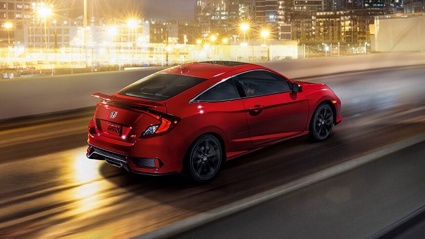 Rear 7/8 passenger's side view of 2020 Honda Civic Si Coupe in Rallye Red driving on highway with a city backdrop.