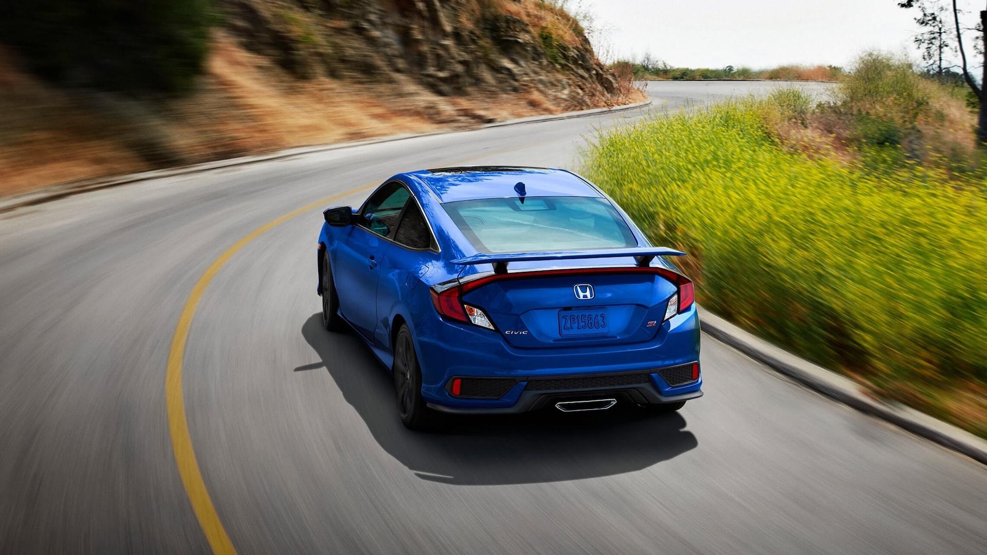 Rear 7/8 driver's side view of 2020 Honda Civic Si Coupe in Aegean Blue Metallic driving on mountain road.