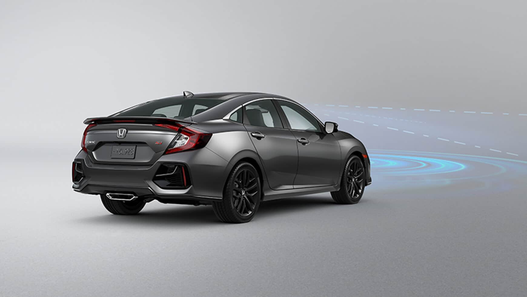 Rear 7/8 driver's side view of 2020 Honda Civic Si Sedan in Modern Steel Metallic demonstrating Collision Mitigation Braking System™ (CMBS™).