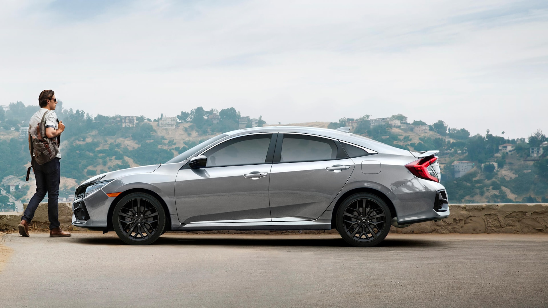 Driver's side view of 2020 Honda Civic Si Sedan in Lunar Silver Metallic parked on the side of a road with a mountain view.