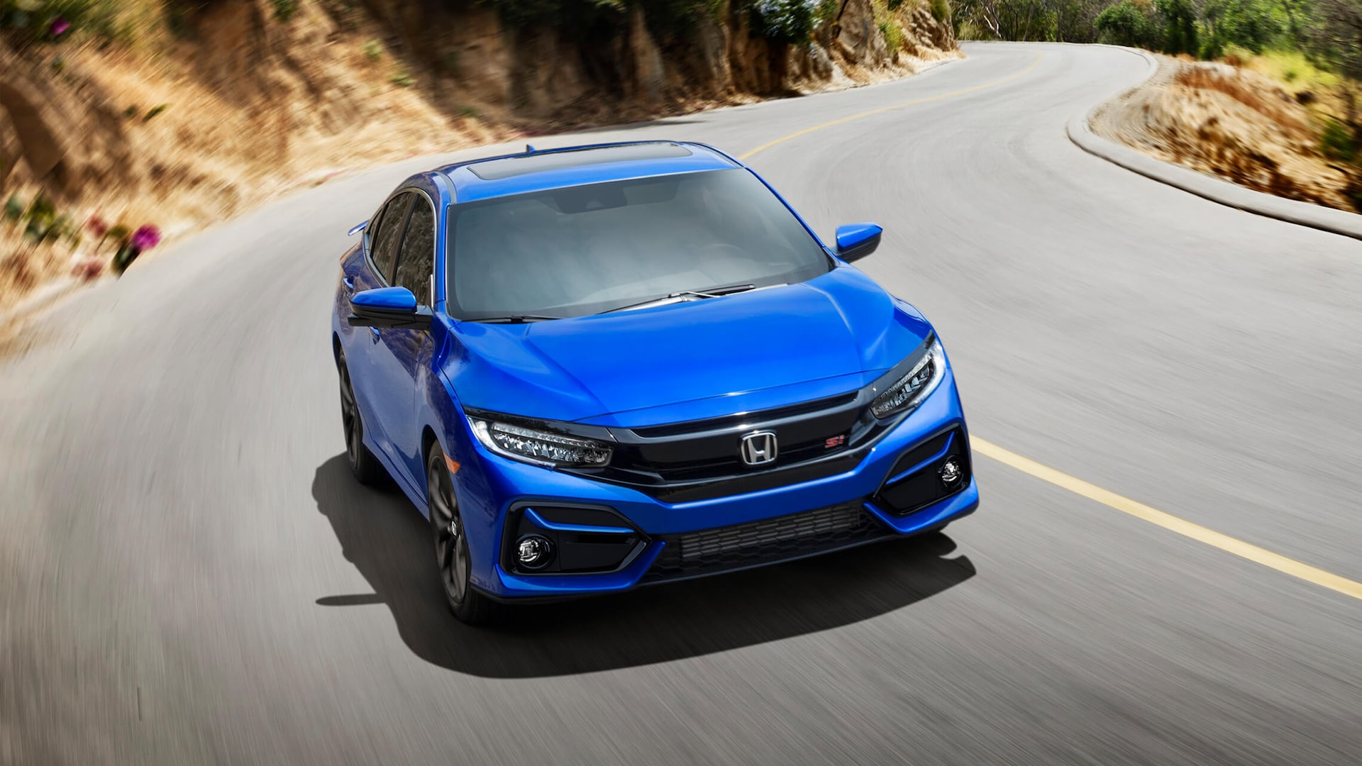 Front passenger's side view of the 2020 Honda Civic Si Sedan in Aegean Blue Metallic driving on side of mountain.