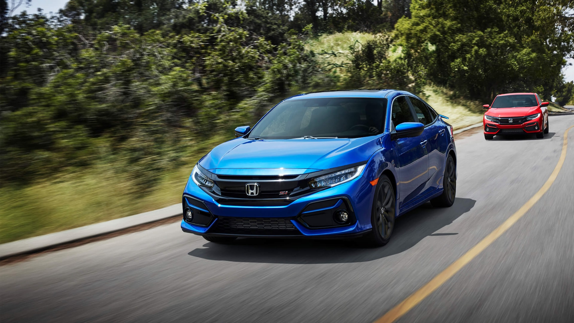Front 3/4 driver's side view of 2020 Honda Civic Si Sedan in Aegean Blue Metallic driving on mountain road.
