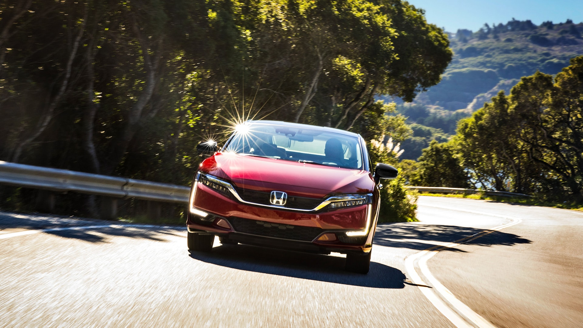 Front view of 2020 Honda Clarity Fuel Cell in Crimson Pearl driving on winding road.