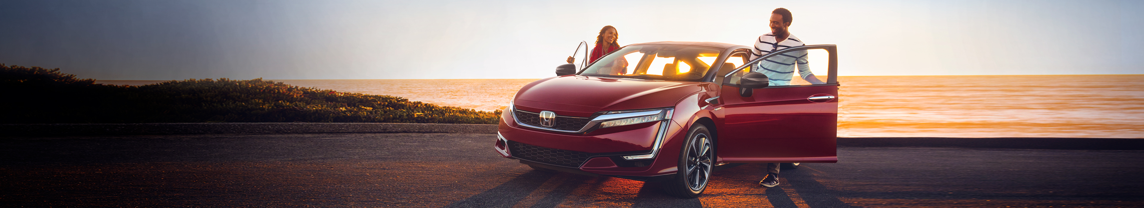 Front driver-side view of the 2020 Honda Clarity Fuel Cell in Crimson Pearl as two people step inside.