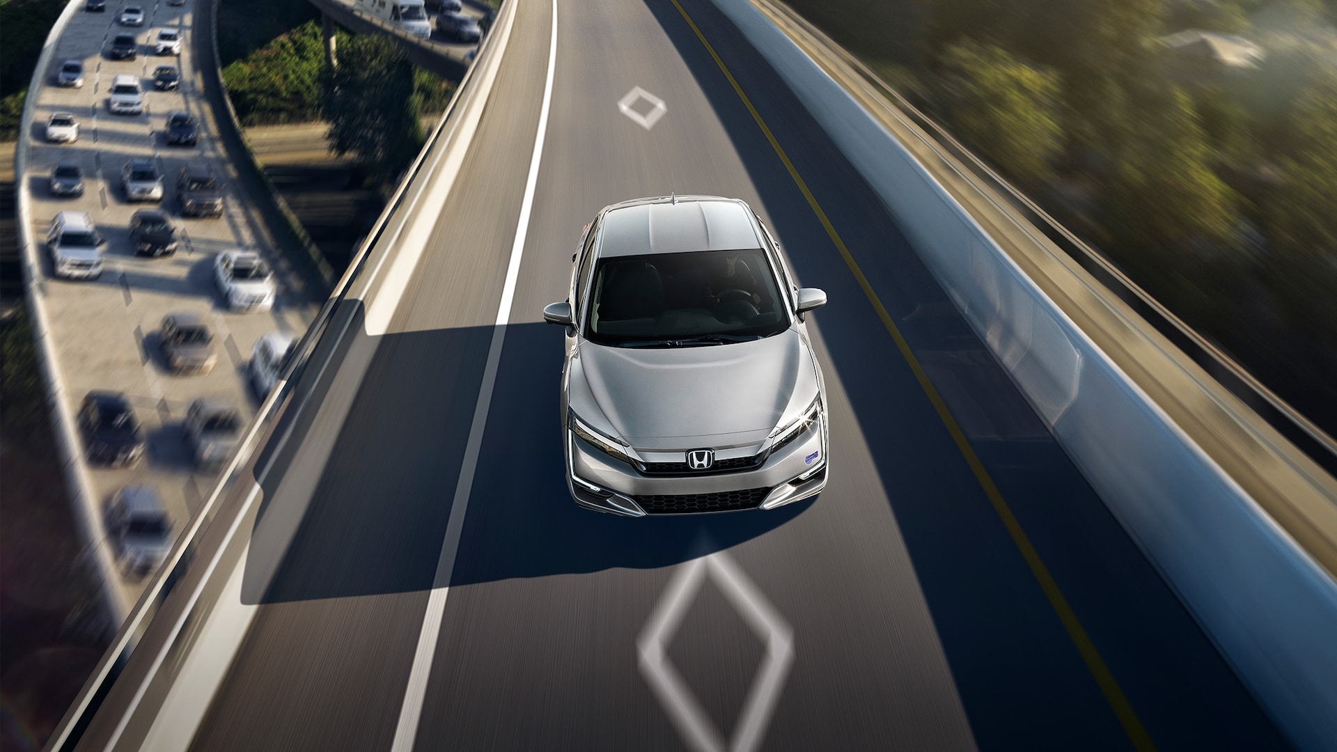 Front overhead of 2020 Clarity Plug-In Hybrid in Solar Silver Metallic driving on HOV access lane.