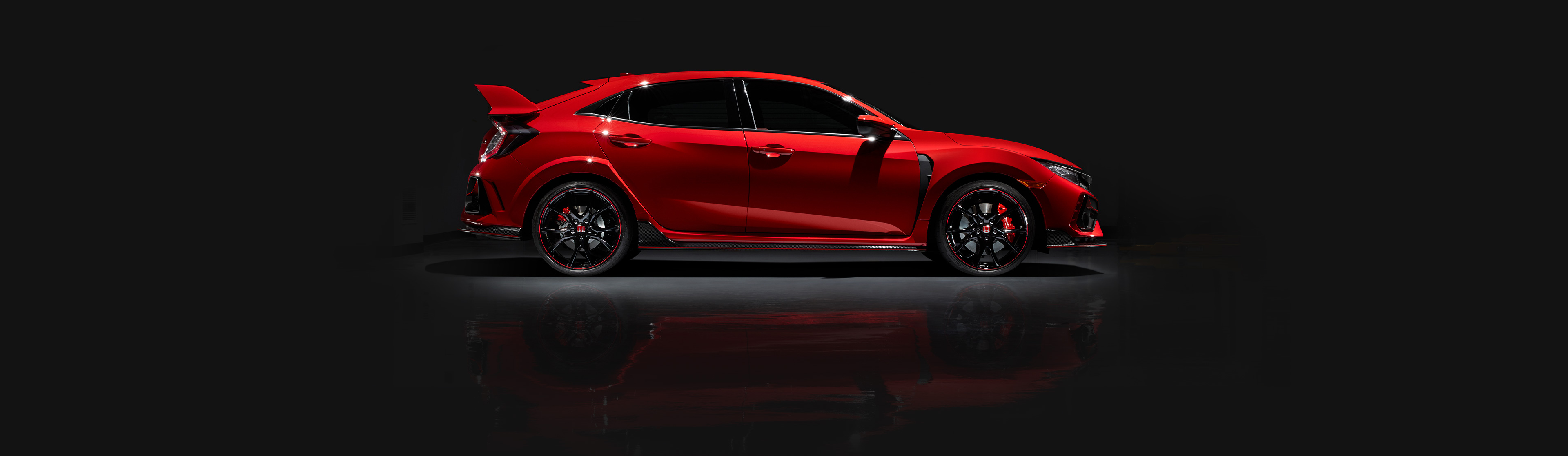 Passenger-side profile view of the 2020 Honda Civic Type R Touring in Rallye Red, parked in a garage.