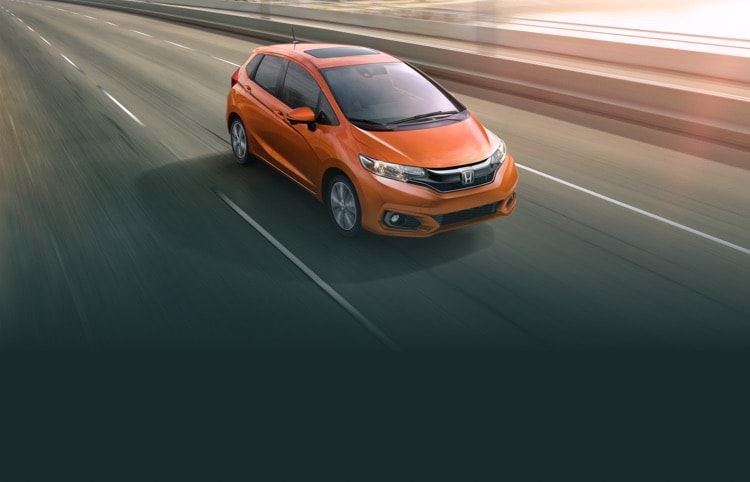 Front passenger side view of the 2020 Honda Fit EX-L in Orange Fury driving on a highway.