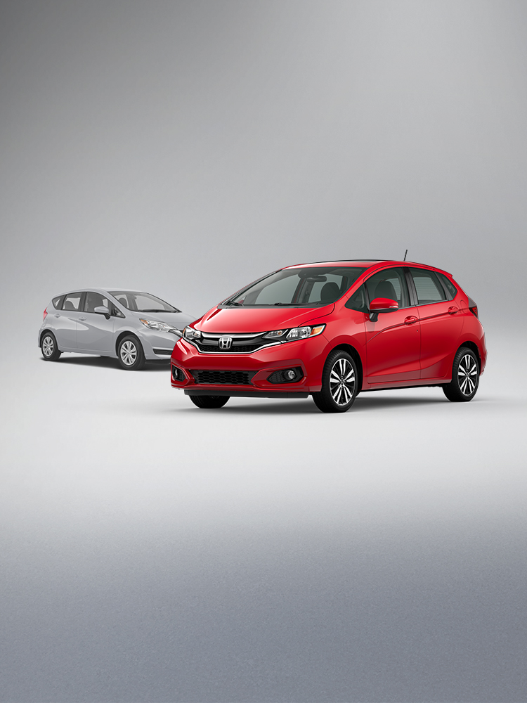 Front driver-side view of the 2020 Honda Fit EX in Milano Red shown parked in front of a competitor vehicle. U.S. News Best Subcompact Car for the Money accolade logo shown.