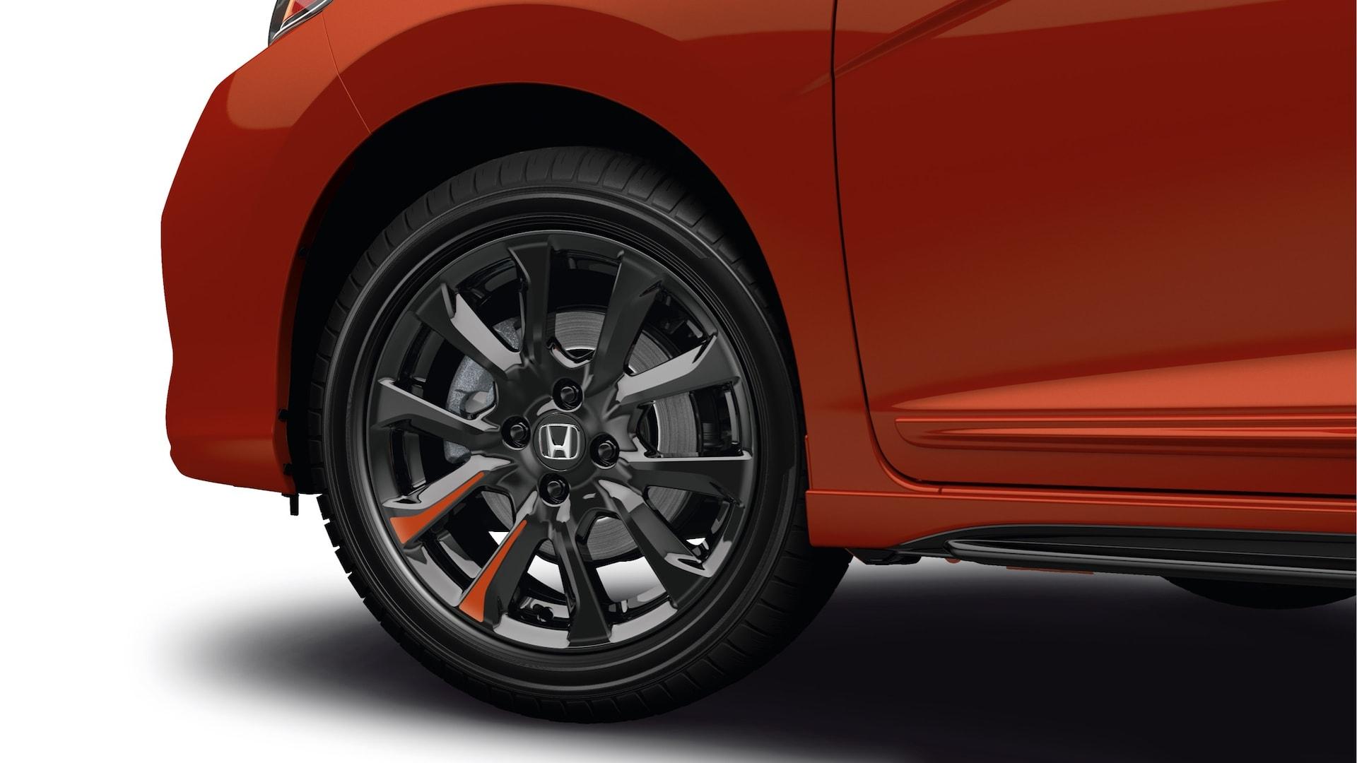 Vista desde el lado del conductor del detalle de las ruedas de aleación de 16pulgadas color negro del Honda Fit2020 en Milano Red.