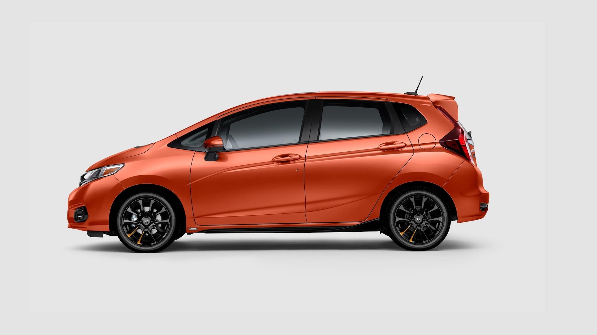Vista de perfil desde el lado del conductor del Honda Fit Sport2020 en Orange Fury con accesorios de Honda Factory Performance®.