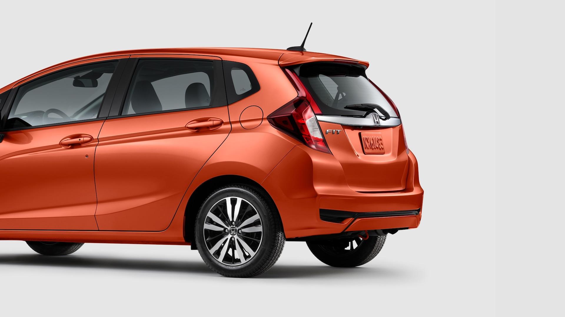 Vista trasera desde el lado del conductor del Honda Fit EX-L2020 en Orange Fury.