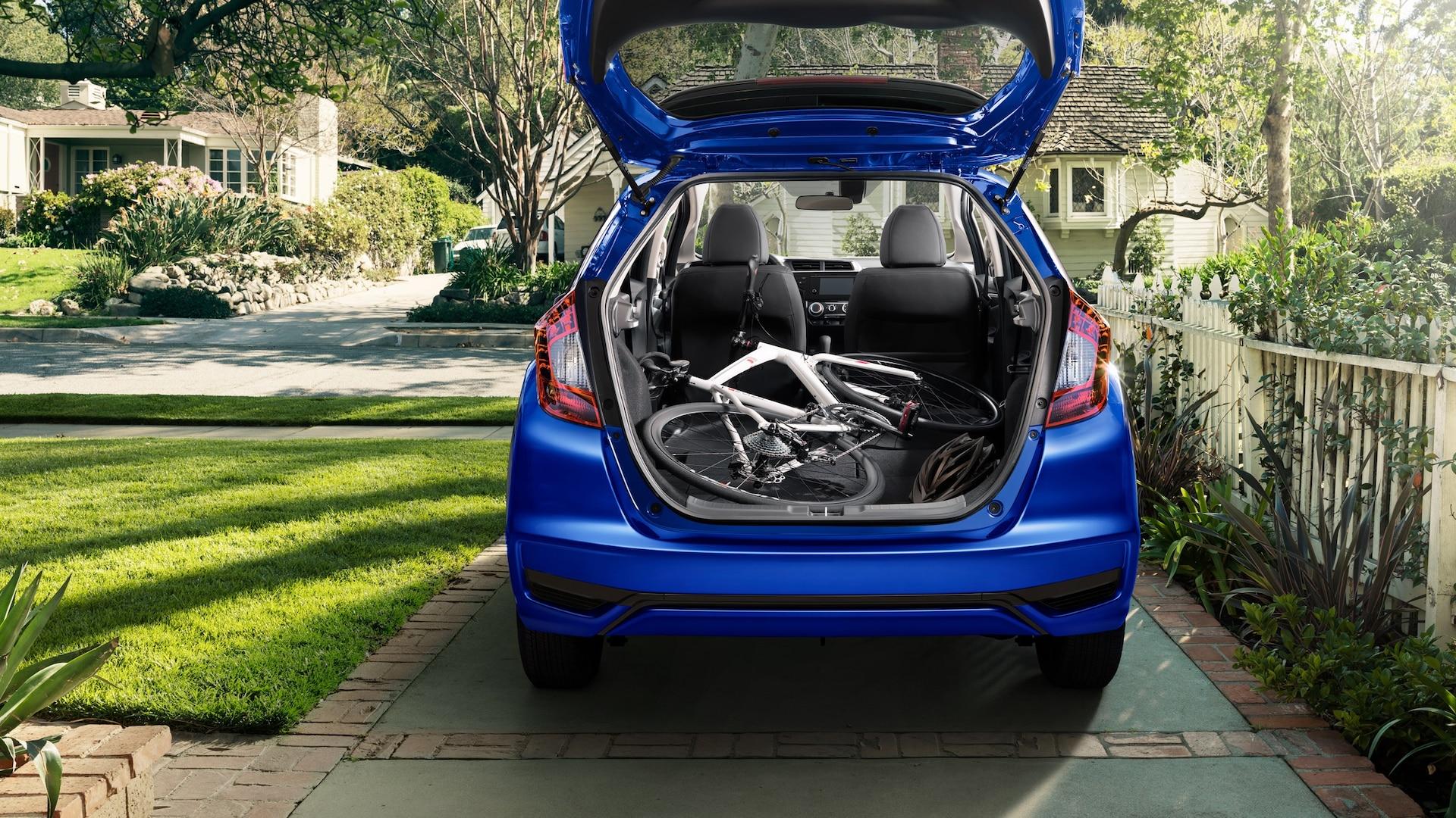 Vista trasera exterior del Honda Fit EX-L2020 en Aegean Blue Metallic con la puerta levadiza abierta y una bicicleta en el área de carga.