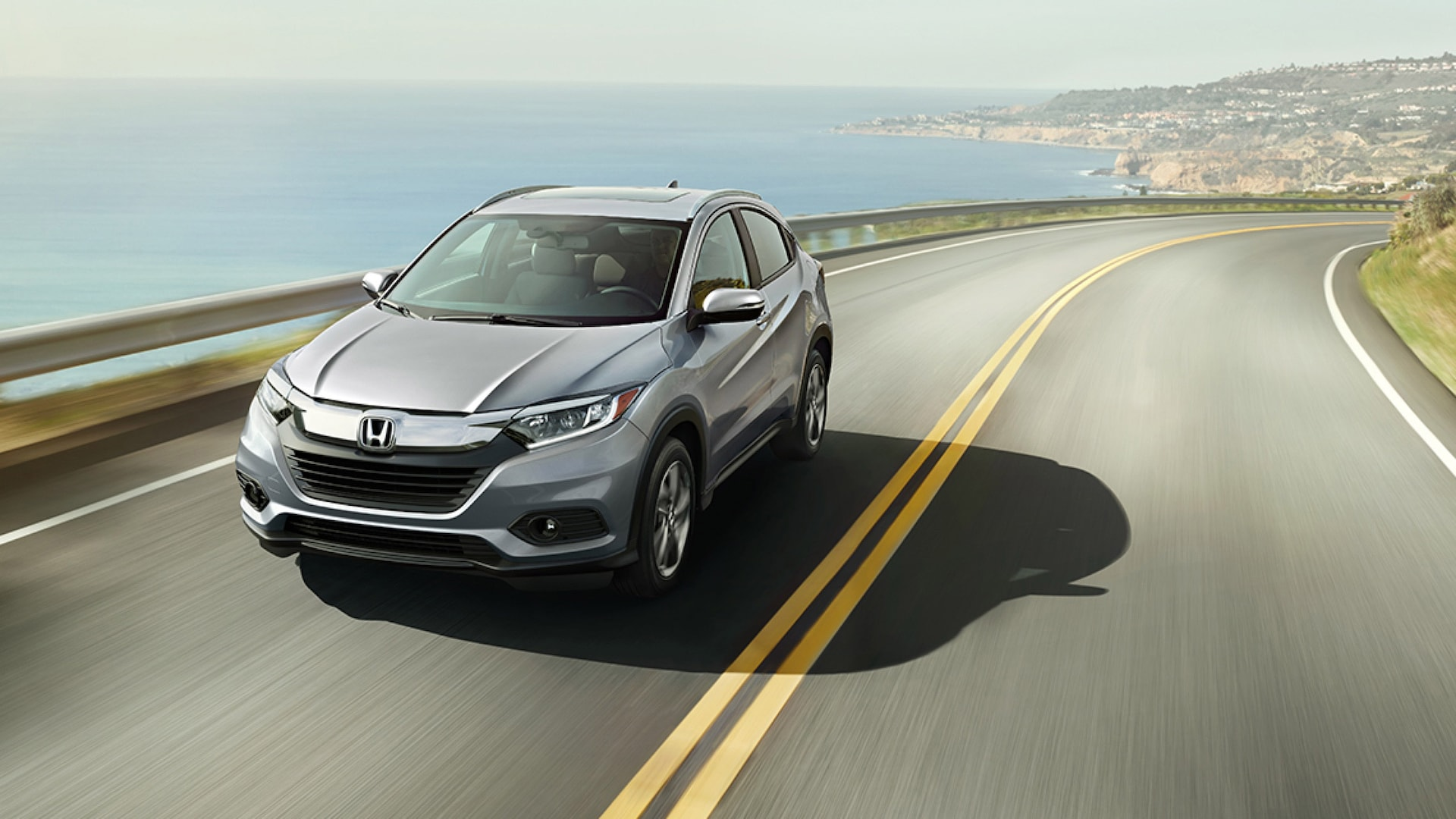 Front 3/4 driver-side view of the 2020 Honda HR-V EX-L in Lunar Silver Metallic driving on a highway overlooking an ocean.