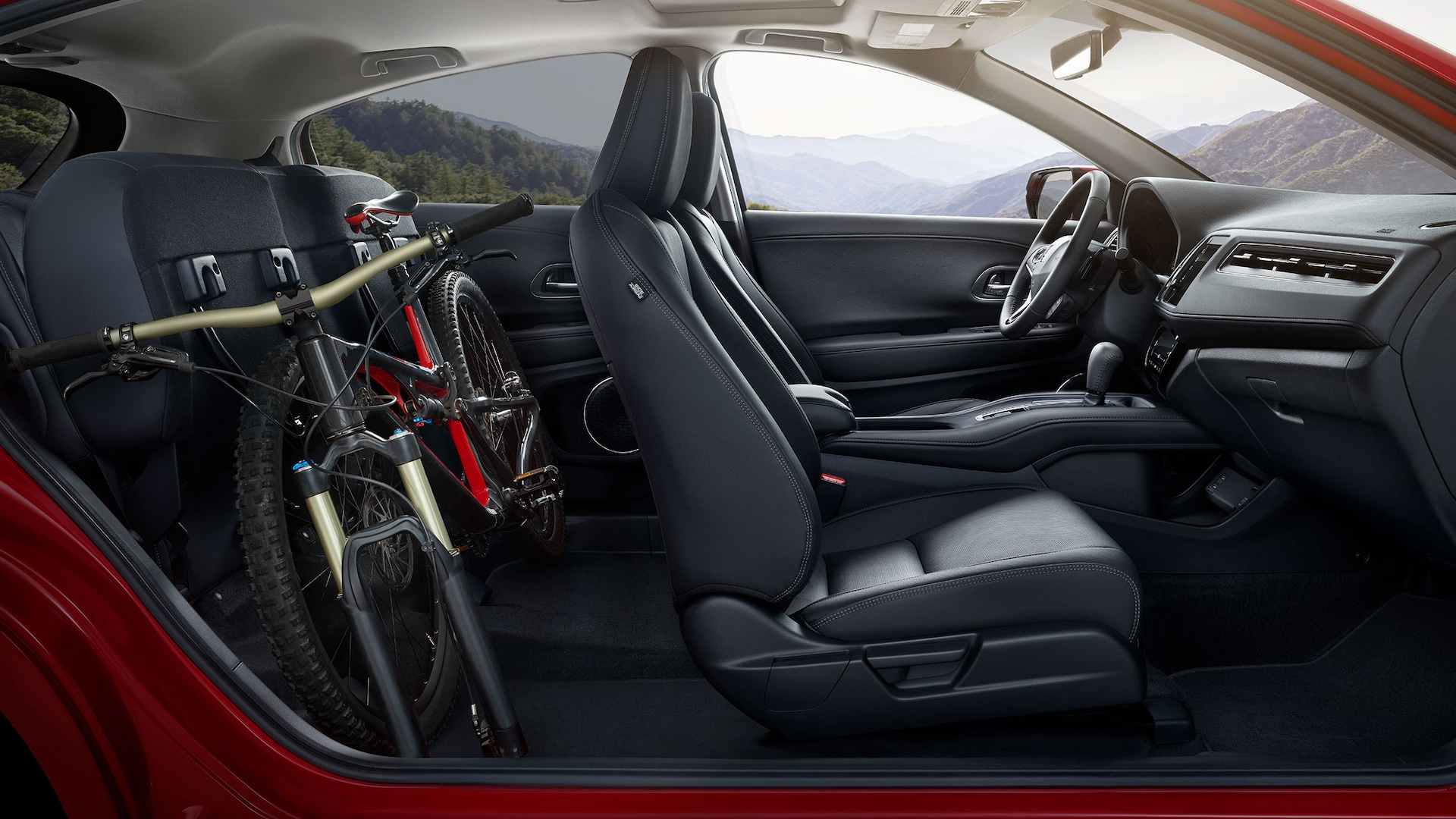 Passenger-side interior view of the 2020 Honda HR-V Touring in Black Leather, with folded rear seats, stowing a bike.