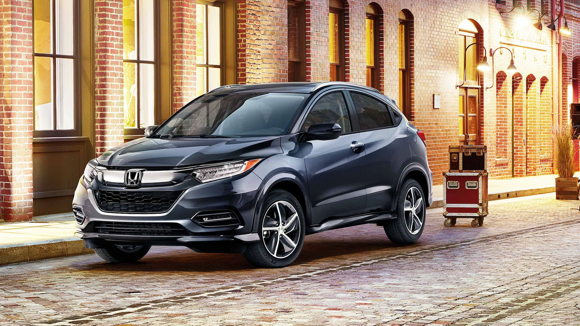 Front driver-side view of the 2020 Honda HR-V Touring in Modern Steel Metallic parked on a cobblestone driveway.