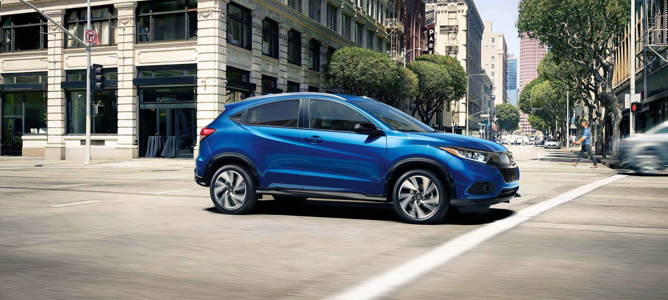 Front passenger-side view of the 2020 Honda HR-V Sport in Aegean Blue Metallic driving on city road.