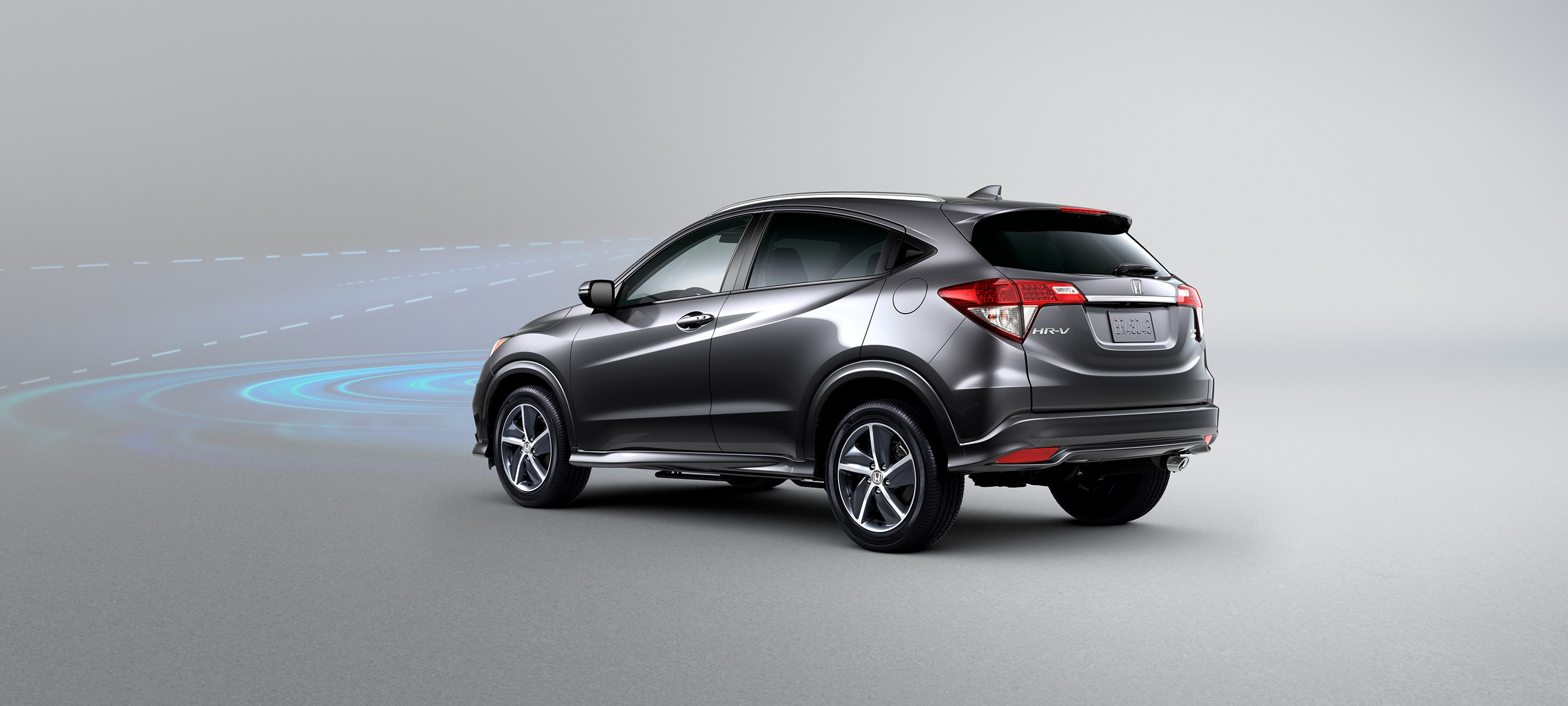 Rear driver-side view of the 2020 Honda HR-V Touring in Modern Steel Metallic with Honda Sensing® illustrated demonstration.