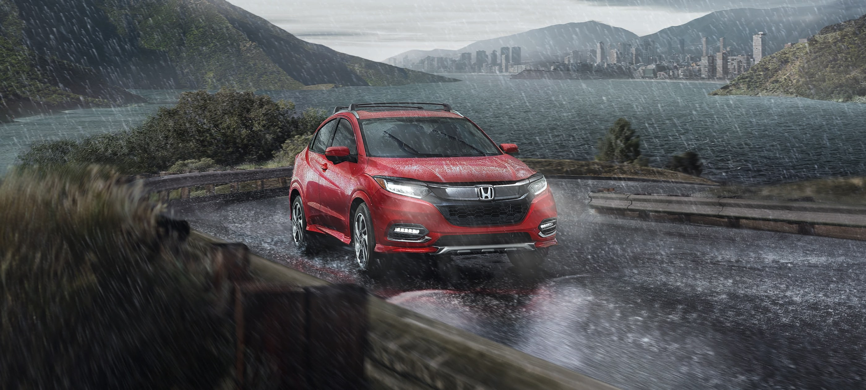 Front passenger-side view of the 2020 Honda HR-V Touring in Milano Red driving through inclement weather.