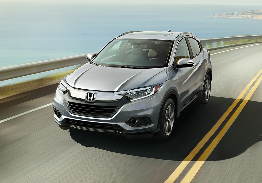 Front driver-side view of the 2020 Honda HR-V EX-L in Lunar Silver Metallic driving down coastal road.