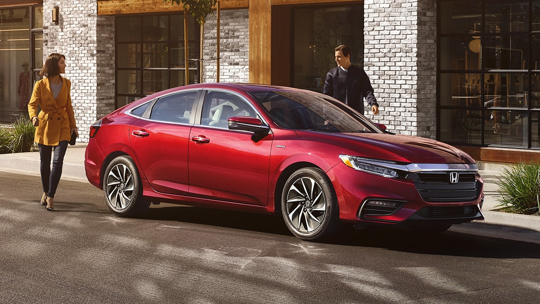 Front 7/8 passenger's side view of 2020 Honda Insight Touring in Crimson Pearl parked at storefront.
