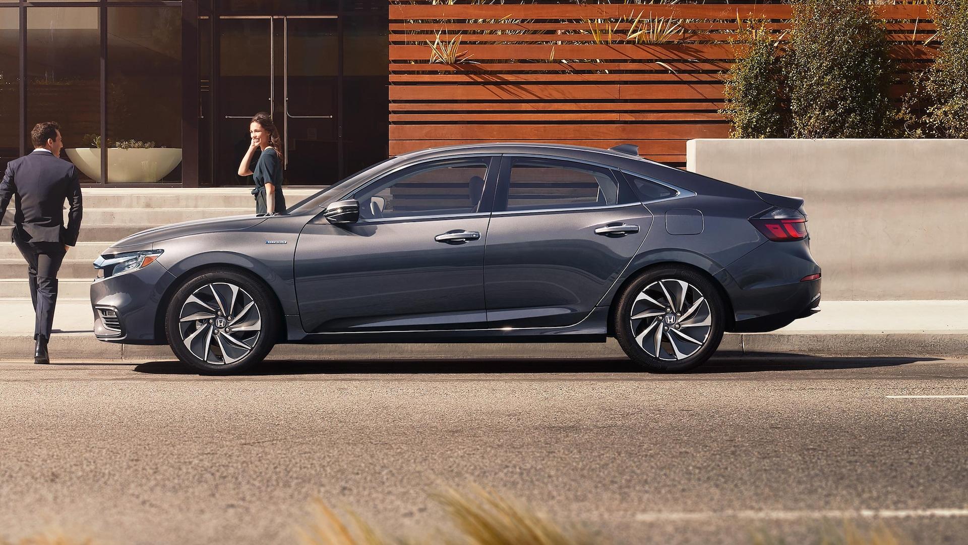 Vista de perfil del lado del conductor del Honda Insight Touring2020 en Modern Steel Metallic estacionado frente a una casa moderna.