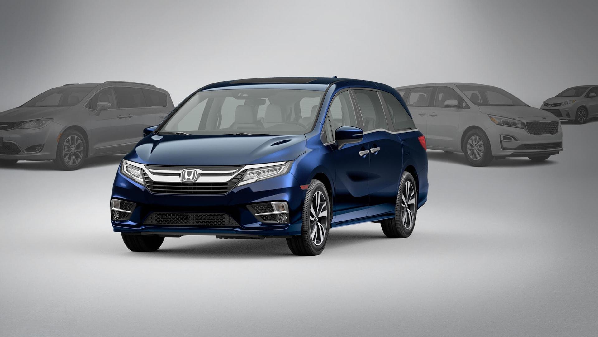 Vista frontal de 3/4 desde el lado del conductor de la Honda Odyssey2020 en Obsidian Blue Pearl estacionada frente a la competencia.
