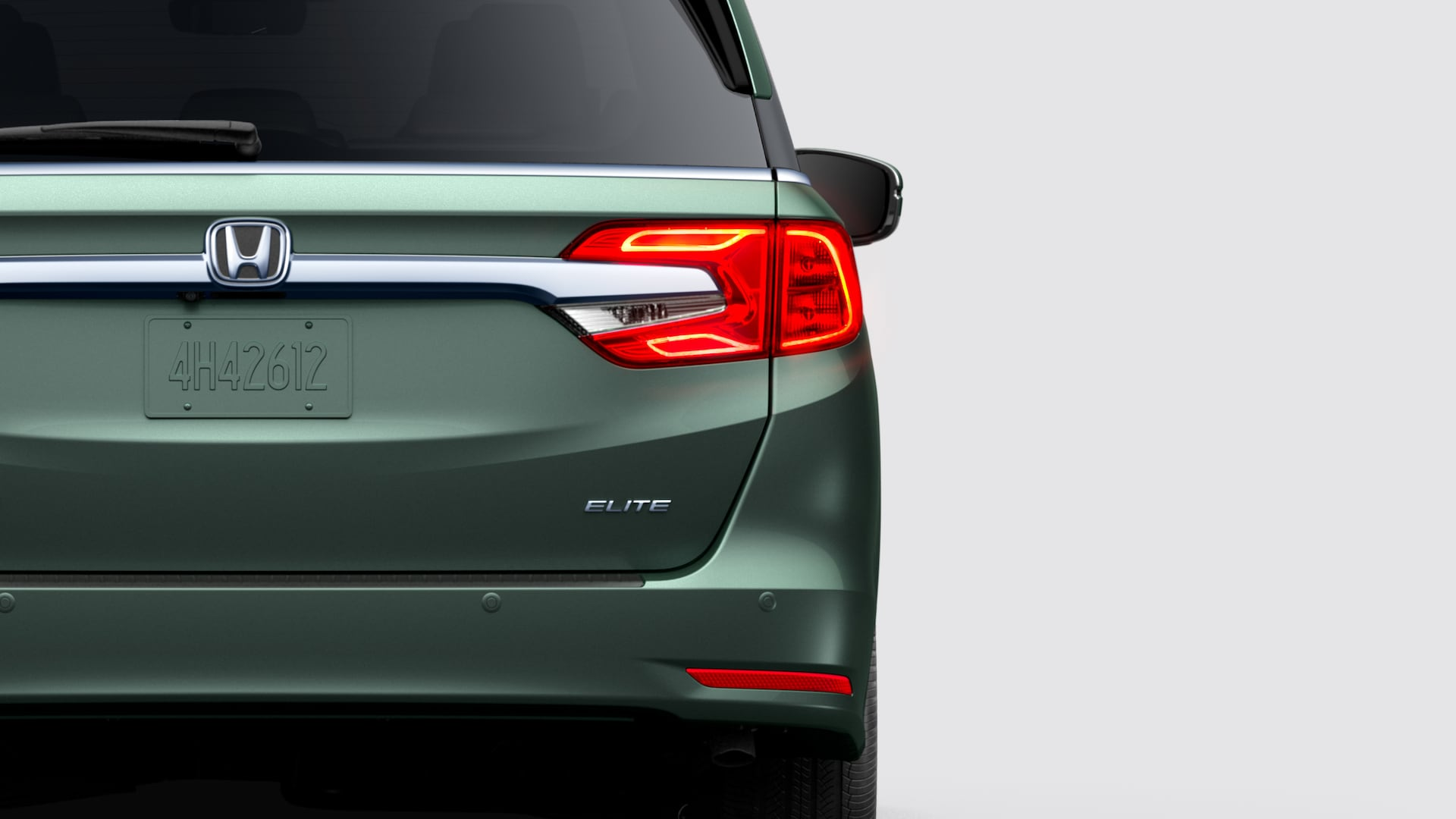 Rear close-up view of driver-side taillight on 2020 Honda Odyssey Elite in Forest Mist Metallic.
