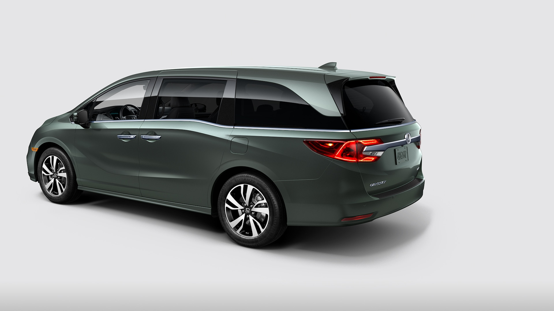 Rear 7/8 driver-side view of 2020 Honda Odyssey Elite in Forest Mist Metallic.
