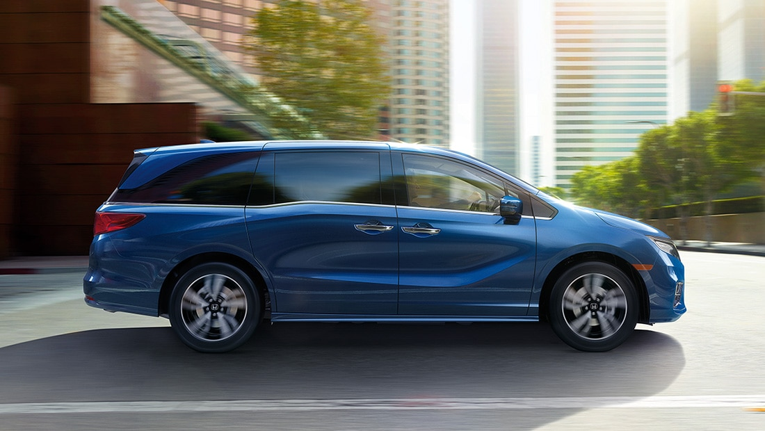 Passenger-side profile view of 2020 Honda Odyssey Elite in Obsidian Blue Pearl driving in city environment.