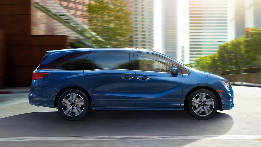 Vista de perfil desde el lado del pasajero de la Honda Odyssey Elite2020 en Obsidian Blue Pearl conduciendo por un entorno urbano.