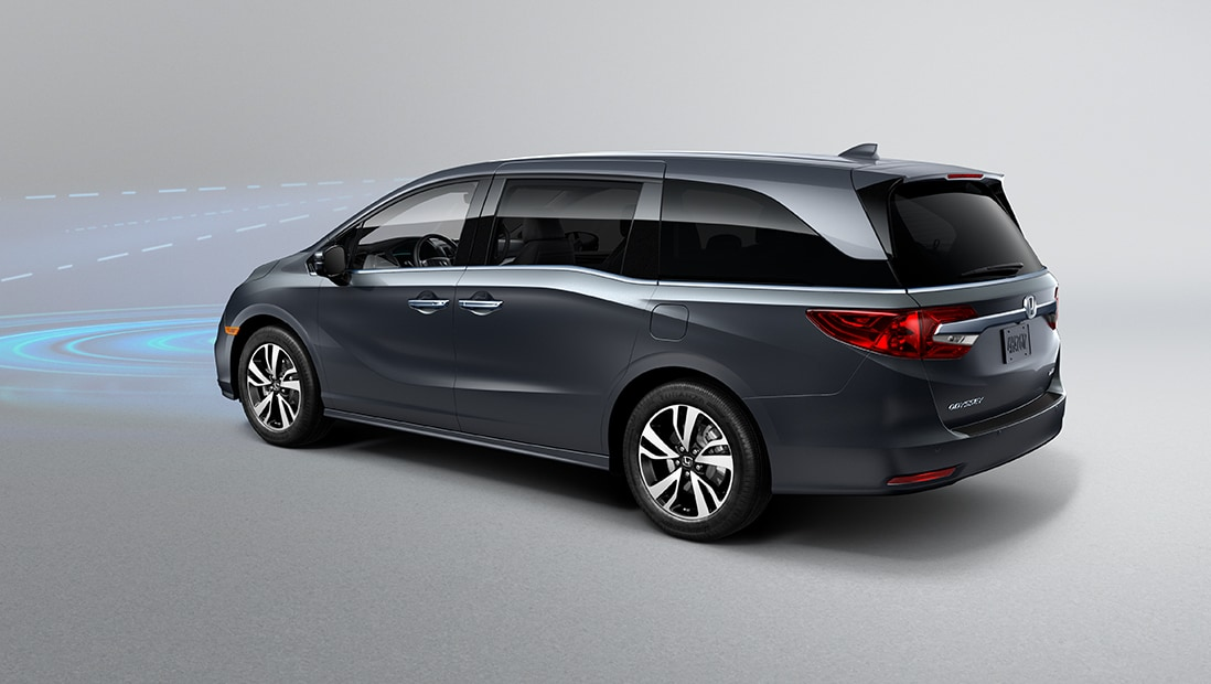Rear 7/8 driver-side view of 2020 Honda Odyssey Elite in Modern Silver Metallic demonstrating Collision Mitigation Braking System™ (CMBS™).
