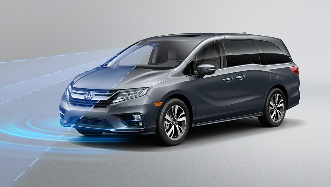 Front 3/4 driver-side view of 2020 Honda Odyssey Elite in Modern Silver Metallic demonstrating Road Departure Mitigation System (RDM).