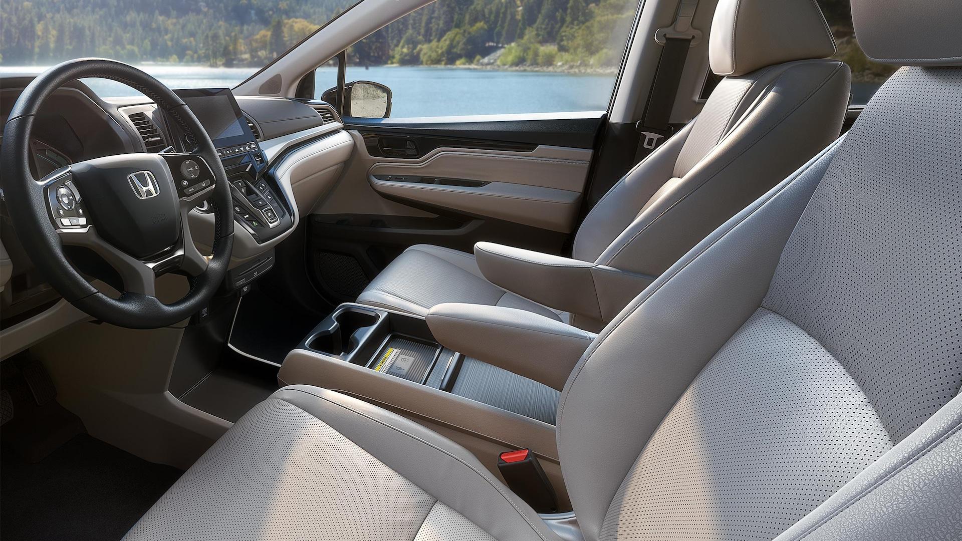 Vista interior desde el lado del conductor del volante y los asientos delanteros en la Honda Odyssey Elite2020 con Gray Leather.