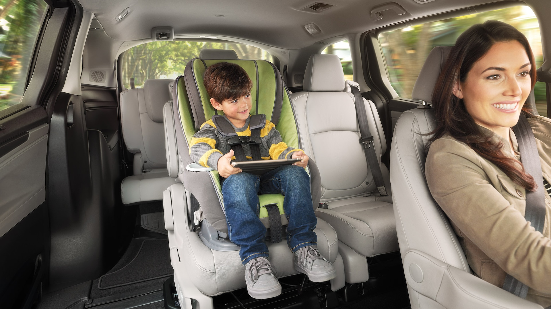 Interior view of Magic Slide® 2nd-row seats, with woman driving and child in rear car seat, in 2020 Honda Odyssey Elite with Gray Leather.