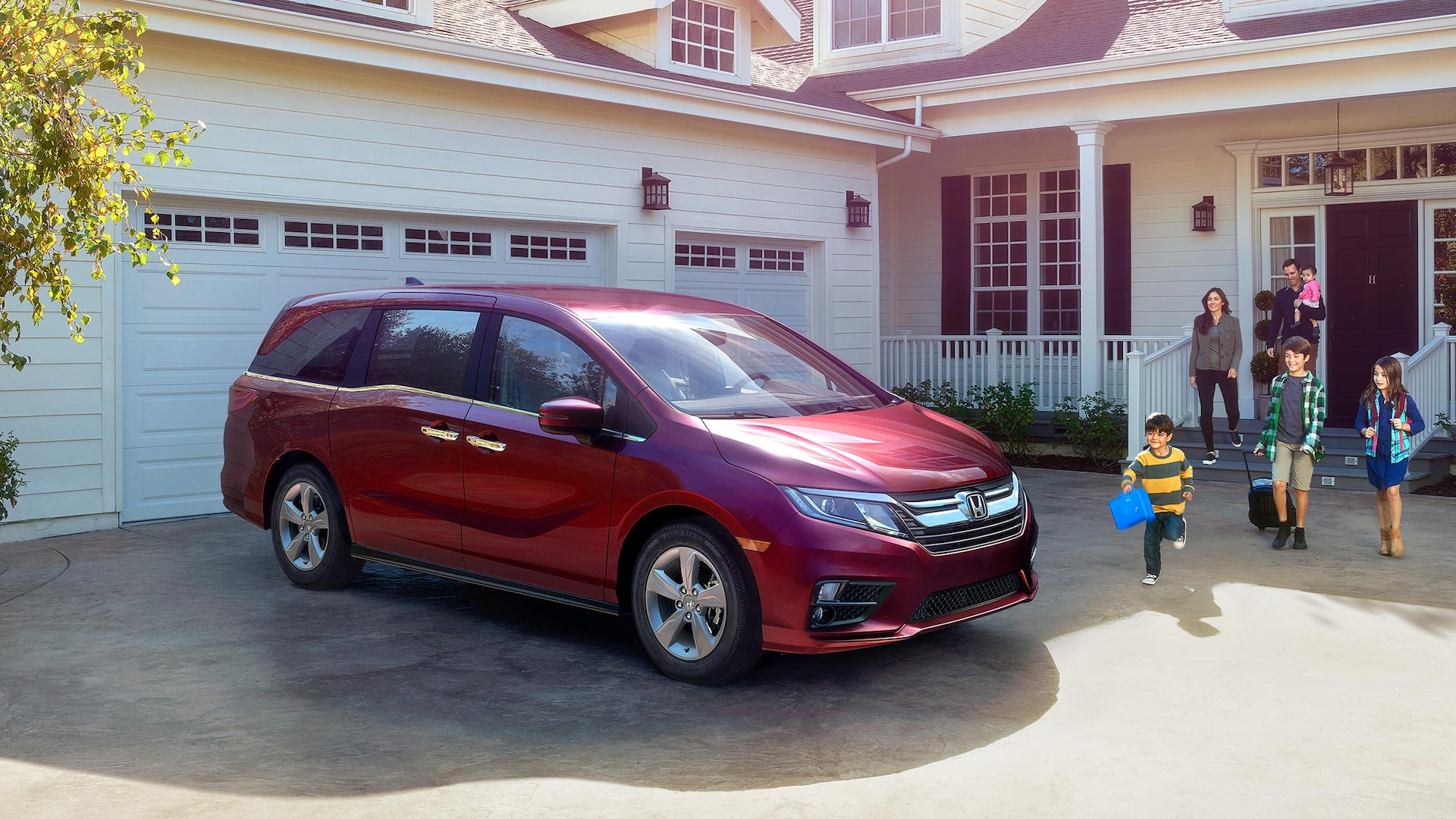 Front 3/4 passenger-side view of 2020 Honda Odyssey Elite in Deep Scarlet Pearl parked in front of house.