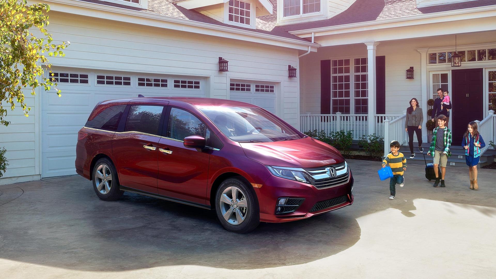 Vista frontal de 3/4 desde el lado del pasajero de la Honda Odyssey Elite2020 en Deep Scarlet Pearl estacionada frente a una casa.