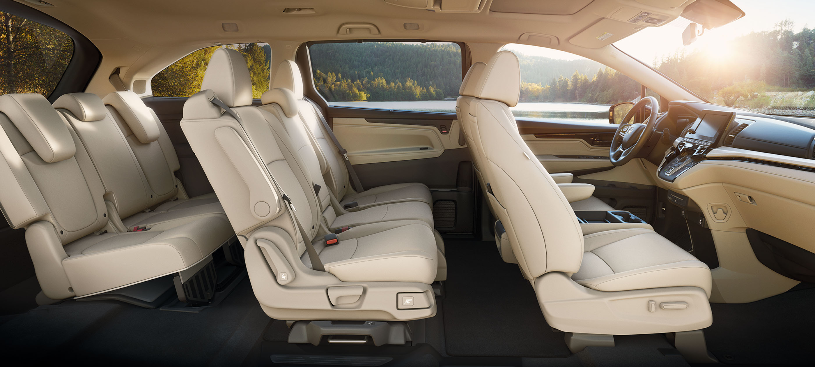 Interior passenger-side profile view of front and rear seats in the 2020 Honda Odyssey with Beige Leather.