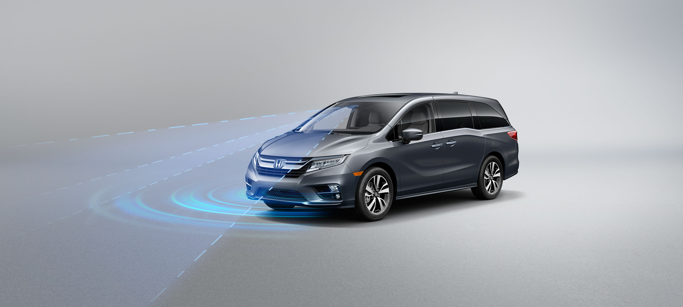 Front driver-side view of the 2020 Honda Odyssey in Forest Mist Metallic, with illustrated Honda Sensing® graphics demonstrating Road Departure Mitigation System.