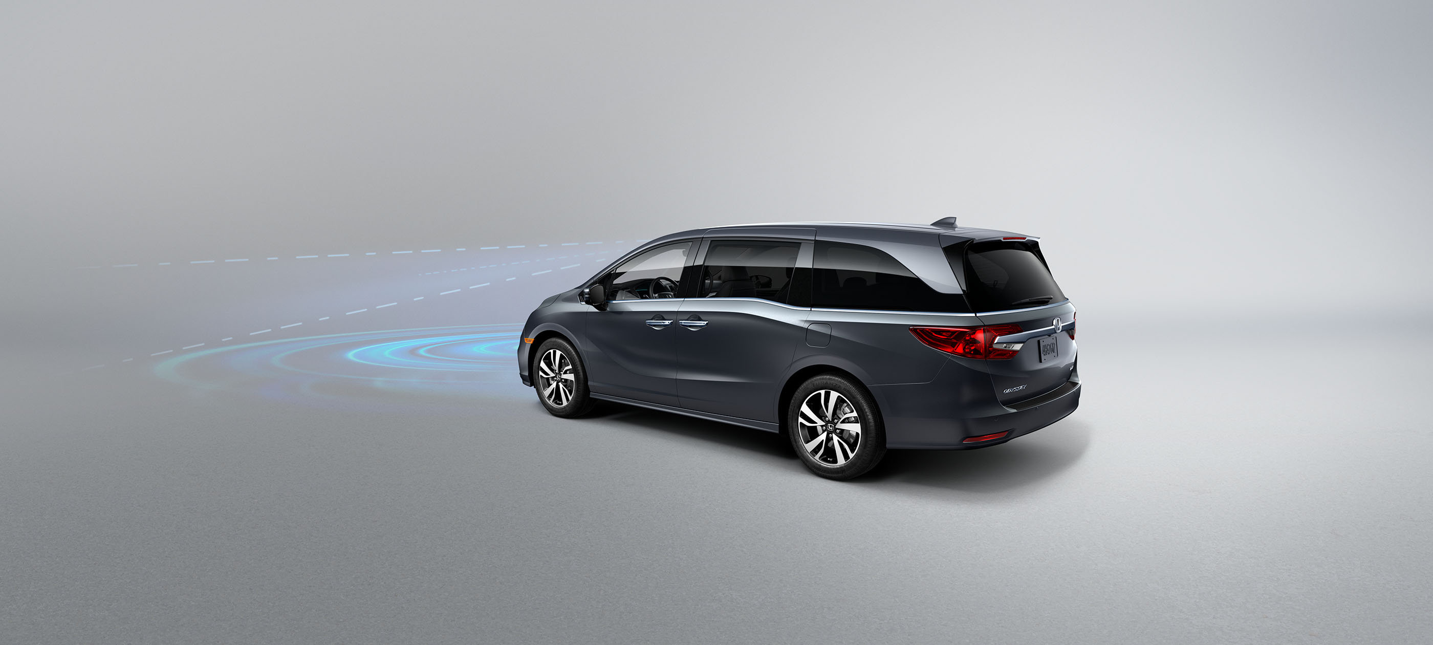 Front driver-side view of the 2020 Honda Odyssey in Forest Mist Metallic, with illustrated Honda Sensing® graphics demonstrating Collision Mitigation Braking System™.