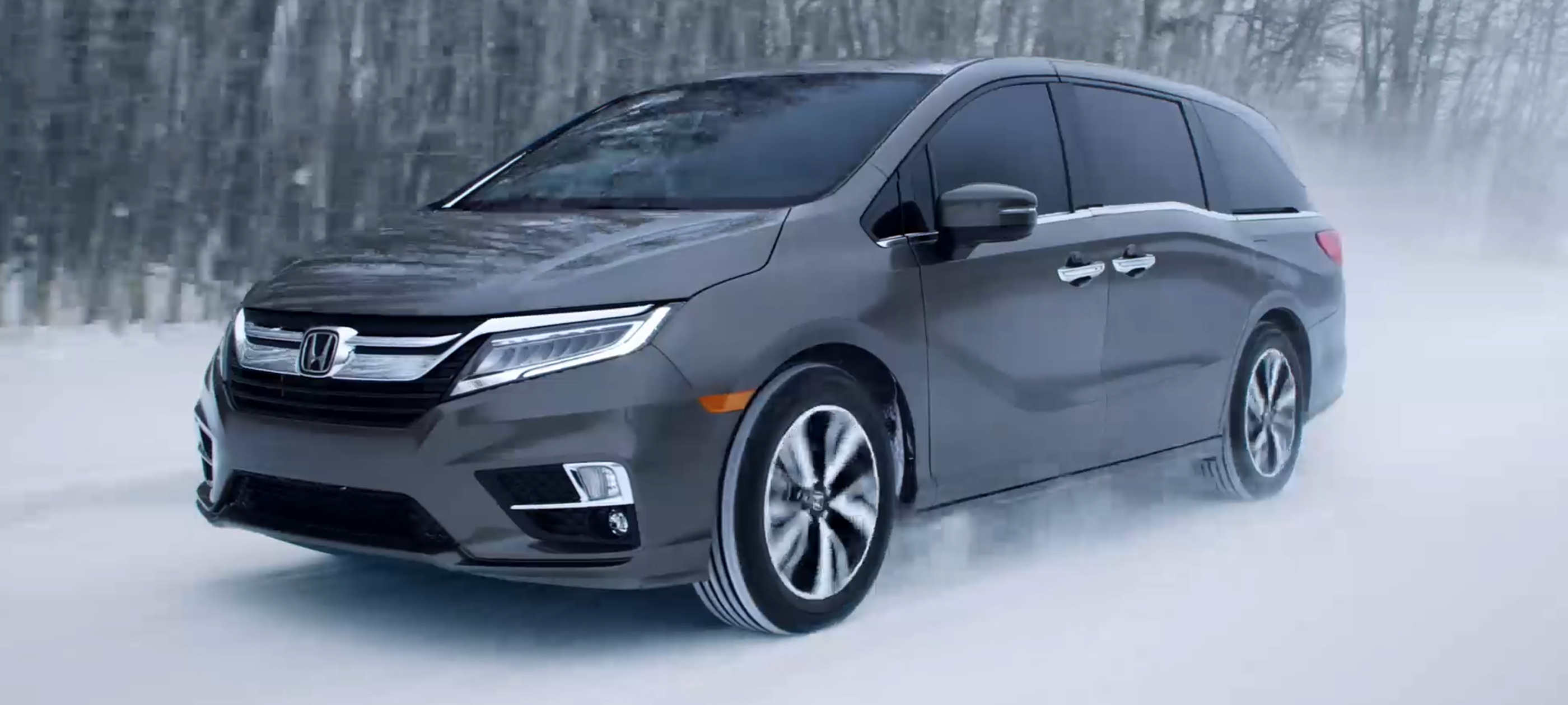 Front driver-side view of the 2020 Honda Odyssey in Modern Steel Metallic driving on a snow-covered road.