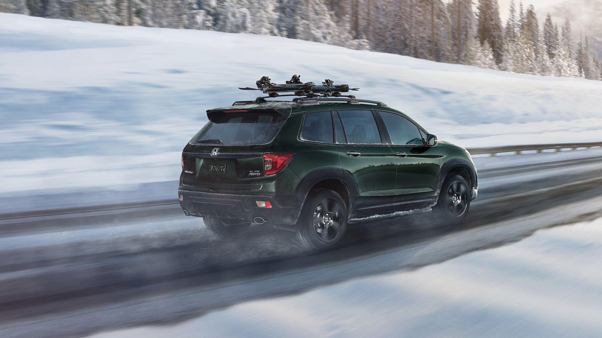 Passenger-side rear 3/4 view of 2020 Honda Passport AWD Elite in Black Forest Pearl with accessory ski/snowboard attachment driving on a snowy mountain road.