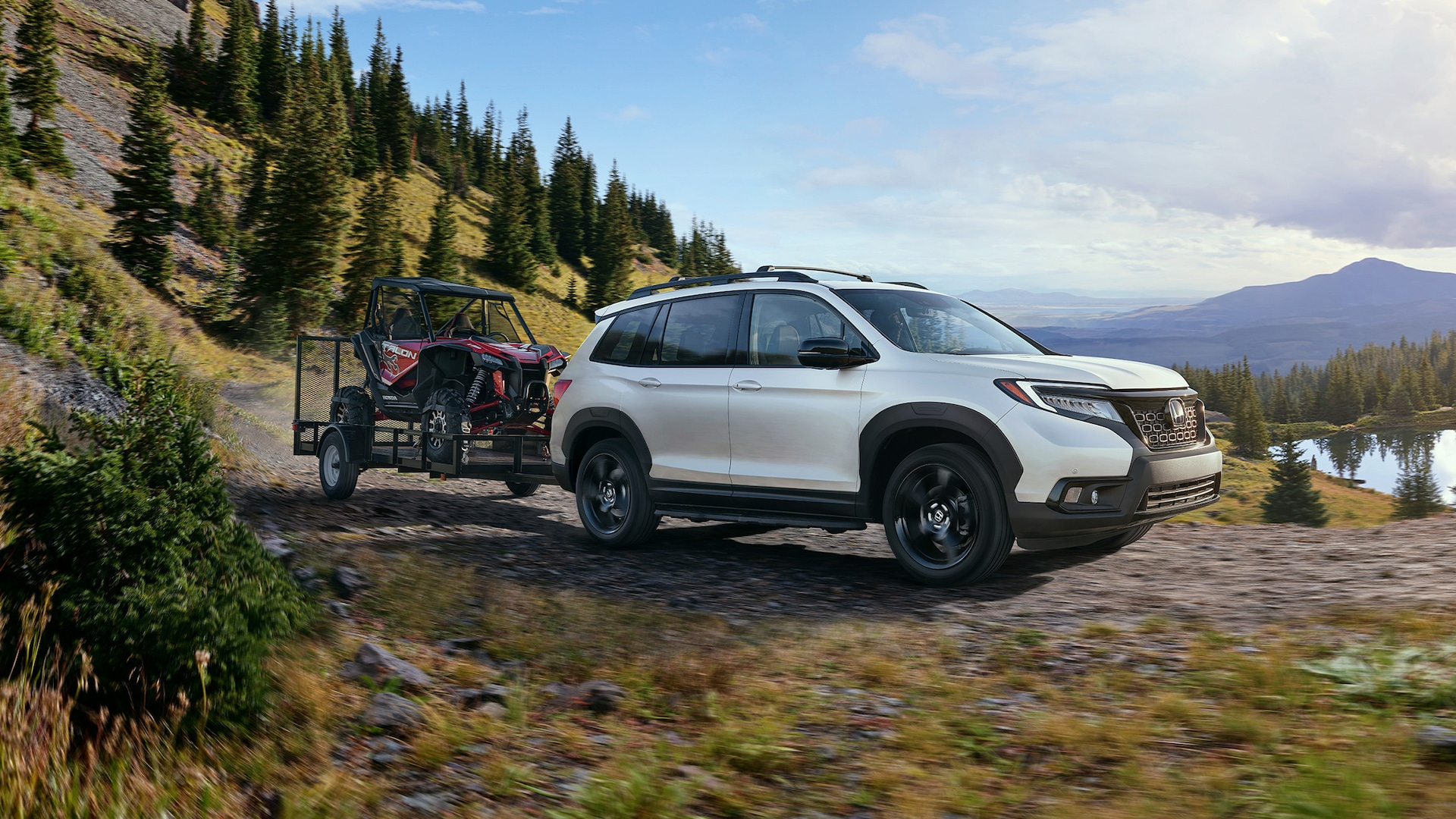 Passenger-side front 7/8 view of 2020 Honda Passport Elite in Platinum White Pearl with accessory tow hitch.