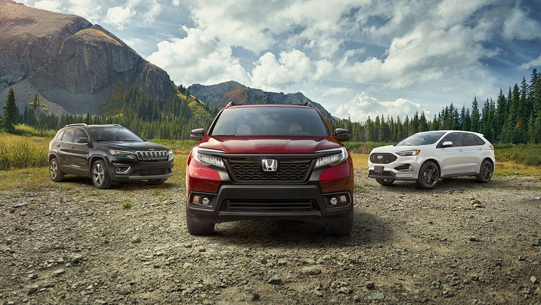 Front view of 2020 Honda Passport Elite, in Deep Scarlet Pearl, parked on dirt turnout with competitor SUVs and mountains in background.