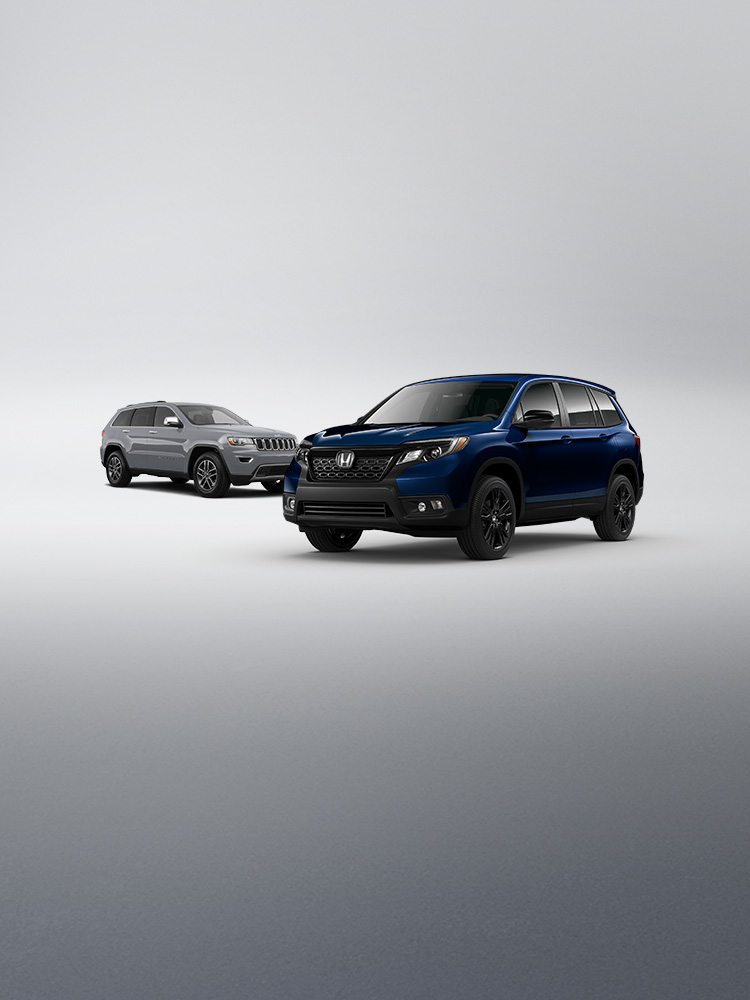 Front passenger-side view of the 2020 Honda Passport Sport in Obsidian Blue Pearl parked in front of 2020 Jeep Grand Cherokee Laredo.