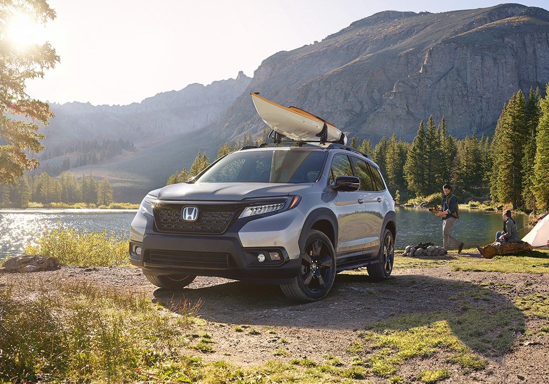 Front driver-side view of the 2020 Honda Passport Elite in Lunar Silver Metallic, with accessory kayak attachment, parked at a lakeside campsite.