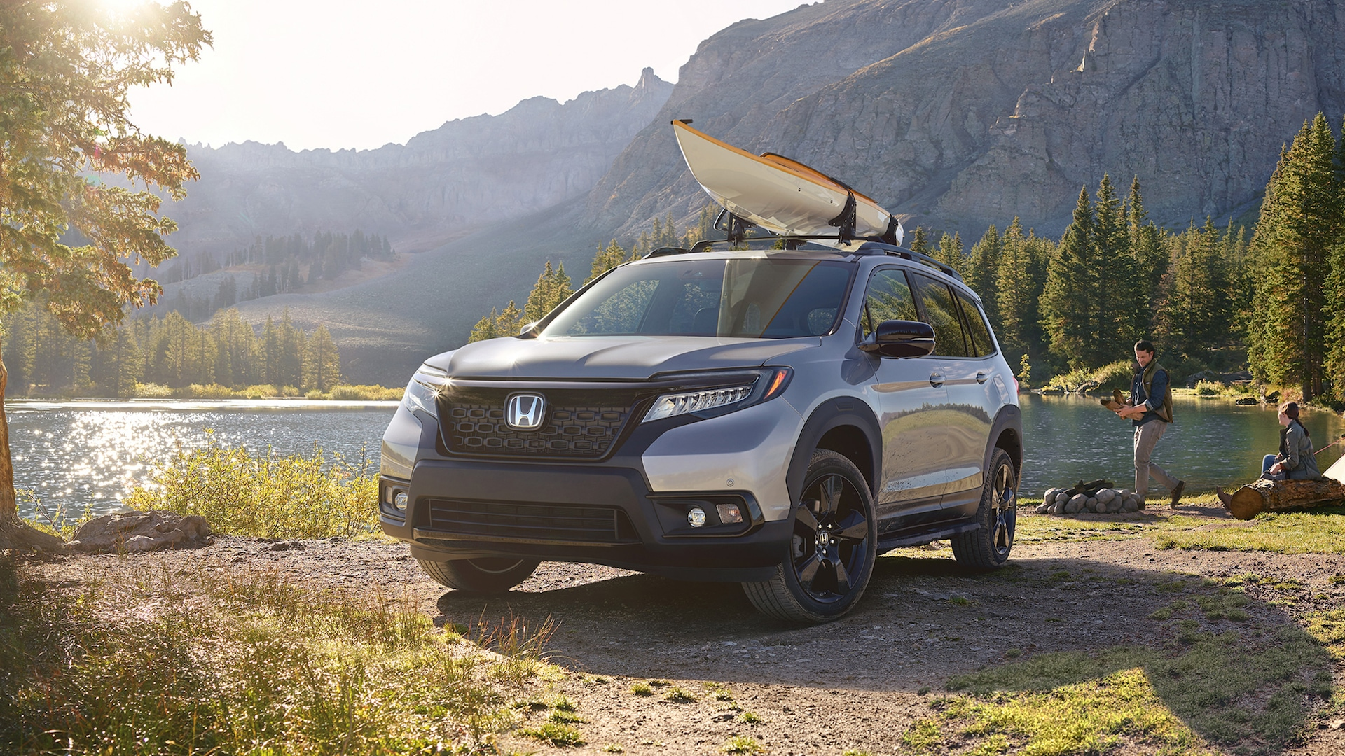 Driver-side front 3/4 view of 2020 Honda Passport Elite in Lunar Silver Metallic, with accessory kayak attachment, parked at a lakeside campground with male and female campers.
