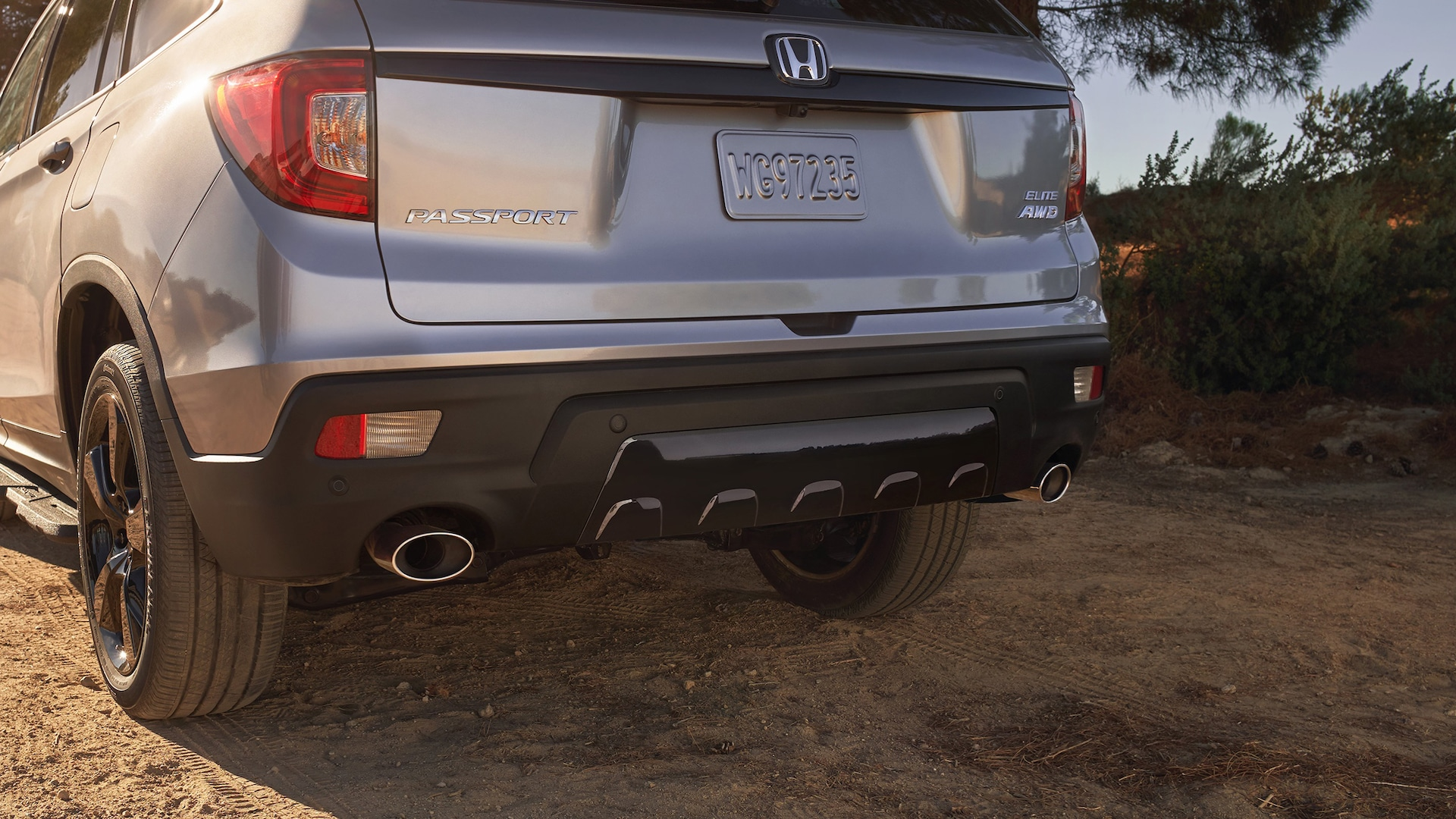 Dual exhaust finishers with parking sensors on the 2020 Honda Passport Elite in Lunar Silver Metallic.