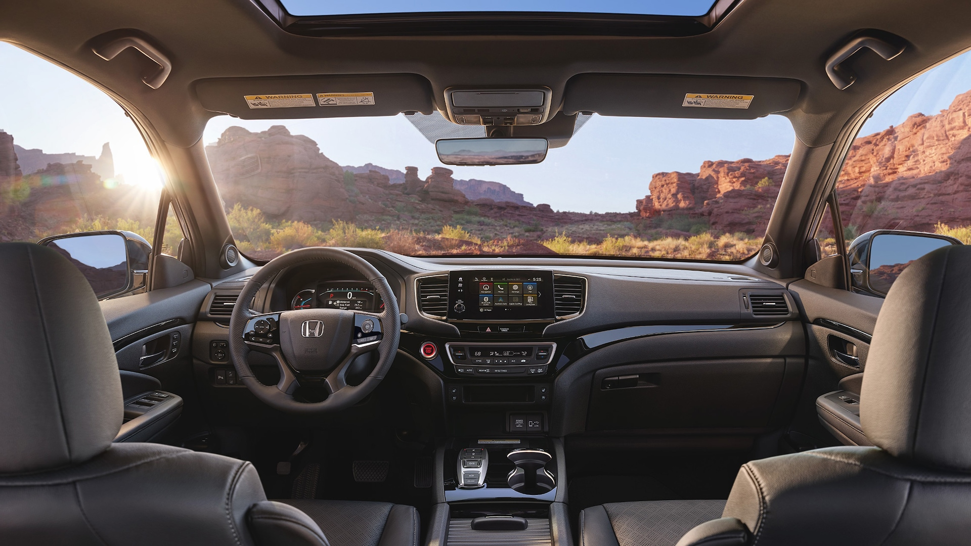 2020 Honda Passport Elite interior view with Black Leather interior showing the major instrument panel, featuring Apple CarPlay® integration on the Display Audio touch-screen.