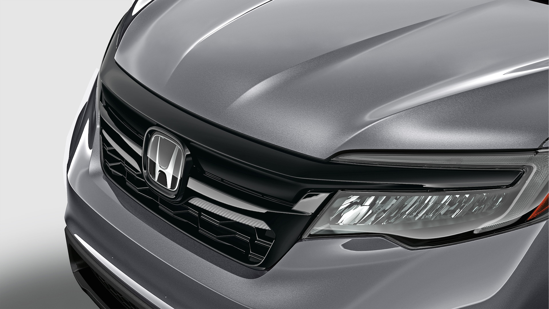 Front grille carbon inserts detail in black on 2020 Honda Pilot in Modern Steel Metallic.