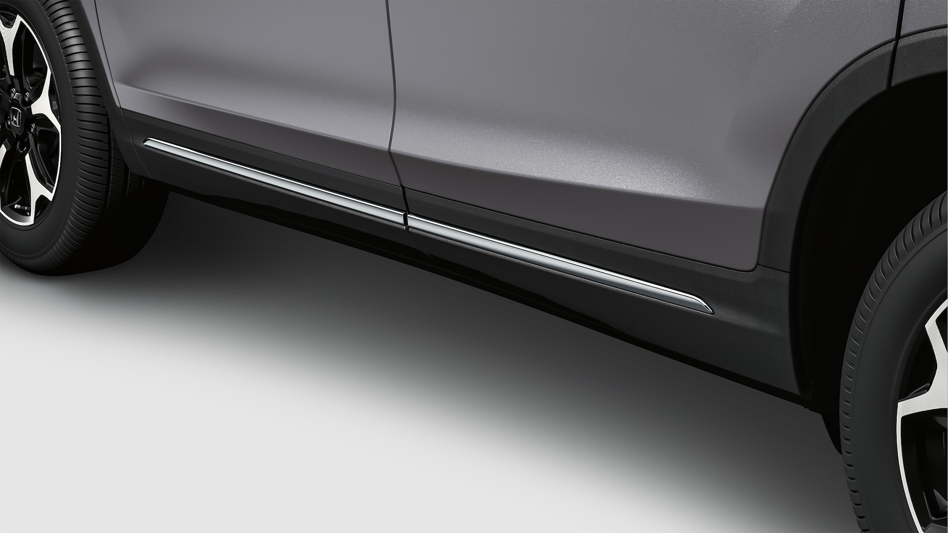 Close-up side view of lower door trim detail on 2020 Honda Pilot in Modern Steel Metallic.